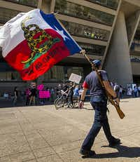 Gun rights advocate Brad McClain carries a rifle and flag as he walks past a rally of gun control advocates outside Dallas City Hall during the NRA Annual Meeting & Exhibits at the Kay Bailey Hutchison Convention Center on Saturday, May 5, 2018, in Dallas.(Smiley N. Pool/Staff Photographer)