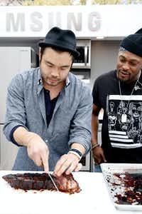 Chef Paul Qui (left) slices meat while singer/songwriter D'Angelo looks on at SXSW 2015 in Austin, Texas(Rick Kern/Getty Images for Samsung)