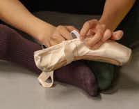 Wang Yuanyuan, artistic director of Beijing Dance Theater, repairs a pointe shoe being used in her new piece <i>Facing the Ocean</i>. The lighthearted duet was one of two new works by Wang that premiered at the TITAS Command Performance.(Ron Baselice/Staff Photographer)