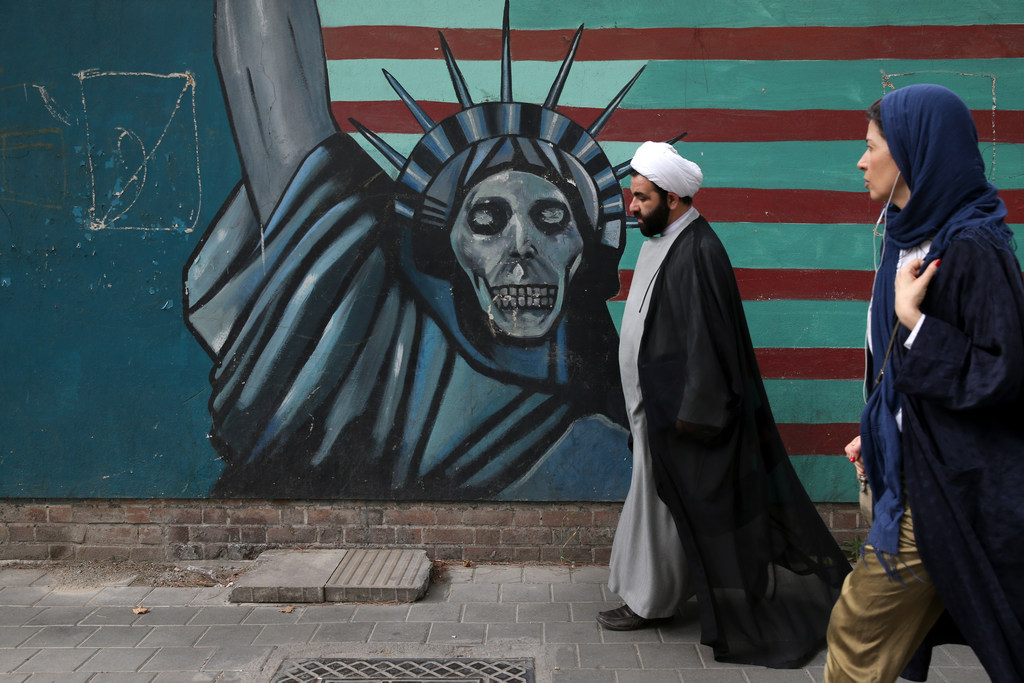A cleric and a woman walk past an anti-U.S. mural painted on the wall of the former U.S. Embassy in Tehran Iran Tuesday May. 8 2018.&nbsp