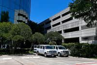 Two white vans are seen near the entrance of an office building where federal agents raided Medoc Health Services on Wednesday.(Jae S. Lee/Staff Photographer)