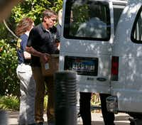 A federal agent loads boxes into a van at Medoc Health Services in Dallas on Wednesday.(Jae S. Lee/Staff Photographer)