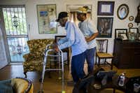 Richard Overton is escorted by family friend Martin Wilford through his living room to the front porch at 10:19 a.m. He spends much of his day there, smoking cigars, snooping on the neighbors, waving at honking cars and greeting visitors.(Ashley Landis/Staff Photographer)