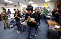Seventh grade students David Rodriquez, Shazy Rubio and Alfredo Garnica (from left) greet visitors by bowing and saying Namaste in a Hindi class at Central Junior High in Bedford on Friday, December 14, 2012. (Lara Solt/Staff Photographer)