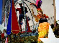 <i>Dallas Morning News</i> columnist Jacquielynn Floyd waves from the Big Tex float as the State Fair of Texas Parade makes its way through downtown Dallas. She donned a Carmen Miranda costume and rode the float for a column about what it's like to be part of the parade that traditionally celebrates the fair's opening day.(2002 File Photo/Staff)