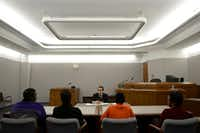 Judge Robert Herrera speaks to a boy, seated with his family and probation officer, who is enrolled in the diversionary program in the mental health court at the Henry Wade Juvenile Justice Center in Dallas on Feb. 10. 2015.(File Photo/<p>Rose Baca</p>)