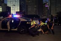 Dallas Police officers take cover behind a police cruiser as shots are fired following a peaceful Black Lives Matter rally July 7, 2016, in downtown Dallas.(File Photo/Staff)