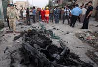 In this picture taken on Sunday, July 14, 2013, security forces inspect the scene of a car bomb attack in Basra, Iraq. Ramadan is shaping up to be the deadliest in Iraq since a bloody insurgency and rampant sectarian killings had the country teetering on the edge of civil war more than half a decade ago.(Nabil al-Jurani/AP)