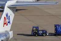 An employee drives with a baggage cart behind an American Airlines jet at DFW Airport.(Vernon Bryant/Staff Photographer)