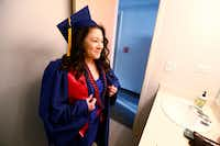 Wendy Birdsall looks at herself in the mirror after putting on her cap and gown before graduation from SMU at the SMU Campus Ministry on Friday.(Nathan Hunsinger/Staff Photographer)