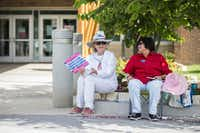 Gubernatorial candidate and former Dallas County Sheriff Lupe Valdez, right, sits with supporter Katherine McGovern outside a primary runoff polling place at Walnut Hill Recreation Center in Dallas earlier on election day.(Ashley Landis/Staff Photographer)