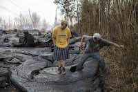 Brandon Lofgreen, left, stands beside Thomas Robinson as he kicks a hole through recently hardened lava from a Kilauea volcano fissure that flowed over a street in the Leilani Estates neighborhood, near Pahoa, Hawaii, Tuesday, May 22.(Tamir Kalifa/The New York Times)