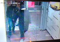 "In this image made from CCTV footage released by Peel Regional Police, two suspects enter a glass doorway of the Bombay Bhel Indian restaurant late Thursday in Mississauga, a suburb of Toronto. Police are searching for the two suspects in connection with the explosion caused by an ""improvised explosive device"" that ripped through the restaurant, wounding 15 people.(Peel Regional Police/AP)"