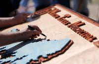 Joe Joplin of North Texas Municipal Water District signs a wooden board with a carved out replica of the future North Texas Municipal Lake during the ground breaking ceremony in unincorporated Fannin County on  May 25.(Vernon Bryant/Staff Photographer)