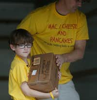 Kaden Newton, 7, and his dad, Keegan Newton, unloaded kid-friendly food items at The Wilkinson Center food pantry in Dallas last year.(Rose Baca/Staff Photographer)