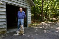 Rick Bragg, 58, stands near his mother's garage with the family dog  in Jacksonville, Ala. (Brynn Anderson/The Associated Press)