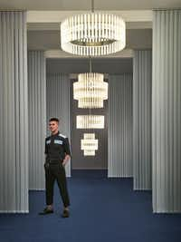 British designer Lee Broom poses with his Aurora Chandeliers. The hand-blown glass bulbs contain a perpendicular LED filament, which refracts against the vertical lines of the reeded glass. (Scott Cooner)
