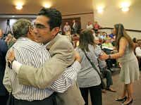 Bhojani's father-in-law, Pyarali Merchant, gave him a hug at last month's ceremony. (Louis DeLuca/Staff Photographer)