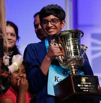 A jubilant Karthik Nemmani holds the Scripps National Spelling Bee Championship Trophy after winning the Scripps National Spelling Bee in Oxon Hill, Md., Thursday, May 31, 2018.(Carolyn Kaster/AP)