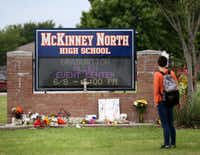 A McKinney North High School student stopped to look at a makeshift memorial while leaving the school after dismissal Monday. (Rose Baca/Staff Photographer)