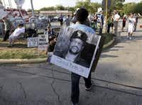 A man wore a placard with James Byrd Jr.'s photo outside the Texas Department of Criminal Justice Huntsville Unit before the 2011 execution of Lawrence Russell Brewer, one of three men convicted in Byrd's death. (David J. Phillip/The Associated Press)