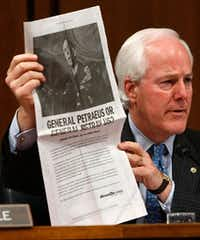 In this 2007 file photo, Sen. John Cornyn, R-Texas, holds up a copy of an ad paid for by MoveOn.org during a hearing of the Senate Armed Services Committee with Gen. David Petraeus. (Alex Wong/Getty Images)