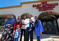 """<p>Abdulkadir Egal (second from right) holds his son Yusuf Egal, 2, in front of his restaurant Iby, with (from left to right)<span style=""""font-size: 1em; background-color: transparent;""""></span><span style=""""font-size: 1em; background-color: transparent;"""">mother-in-law Khadija Farah,</span><span style=""""font-size: 1em; background-color: transparent;""""></span><span style=""""font-size: 1em; background-color: transparent;"""">wife Asia Hersi,</span><span style=""""font-size: 1em; background-color: transparent;""""></span><span style=""""font-size: 1em; background-color: transparent;"""">son Ibrahim Egal, 4,</span><span style=""""font-size: 1em; background-color: transparent;""""></span><span style=""""font-size: 1em; background-color: transparent;"""">son Khalid Egal, 15, and</span><span style=""""font-size: 1em; background-color: transparent;""""></span><span style=""""font-size: 1em; background-color: transparent;"""">daughter Rayann Egal, 12.</span></p>(Jae S. Lee/Staff Photographer)"""