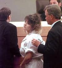 Darlie Routier, on death row for the murder of her 5-year-old son, turns at the close of her court hearing in Dallas on Oct. 30, 1998. Flanking Routier are her attorneys Stephen Cooper (left) and Steve Losch. At rear is Judge Robert Francis. (LM Otero/The Associated Press)