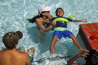 Elizabeth Cisneros, a YMCA swimming instructor, teaches Ridham Babel, 4, how to float on his back at an apartment complex in Irving in 2014.(Brittany Sowacke/Staff Photographer)