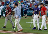 Injured aide Zack Barth (second from left) and injured Rep. Roger Williams, R-Texas, walked off the field before the congressional baseball game last June.(Alex Brandon/The Associated Press)