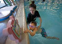 Instructor Ashlee Brannam teaches Truett Roush, 2, how to go back to the wall of the pool during a swim lesson at Jim Montgomery Swim School in Dallas.(Jae S. Lee/Staff Photographer)