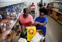 Volunteer Myree Hollins (right) helps client Ardell McNeal get groceries at the CitySquare food pantry in Dallas on June 13.(Rose Baca/Staff Photographer)
