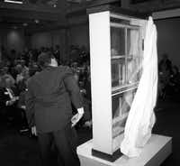"Jeff West and Caruth Byrd, barely visible through the window, unveil the Sniper's Perch  window from the sixth floor that was removed six weeks after the  shooting. The window was one of two ""missing pieces of history"" that were added to the Sixth Floor Museum during a ceremony and reception in 1997.(File Photo/Staff)"