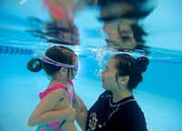 """<p><span style=""""font-size: 1em; background-color: transparent;"""">Olivia Lemmon, 2, gets a swim lesson to become comfortable underwater from instructor Monica Perez during a class at Jim Montgomery Swim School in Dallas. A major technique taught in the classes is how to go back to the wall of the pool.</span></p>(Jae S. Lee/Staff Photographer)"""