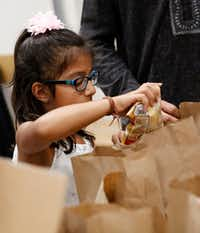 Samaira Verani, 5, packs a snack bag to be donated to various area food pantries at Ismaili Jamatkhana in Plano, Texas on Eid al-Fitr, Friday, June 15, 2018. (Rose Baca/Staff Photographer)