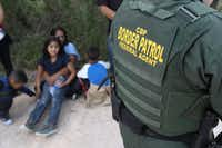 Central American asylum seekers waited as U.S. Border Patrol agents took them into custody on June 12 near McAllen.(John Moore/Getty Images)