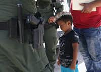 """MISSION, TX - JUNE 12:  A boy and father from Honduras are taken into custody by U.S. Border Patrol agents near the U.S.-Mexico Border on June 12, 2018 near Mission, Texas. The asylum seekers were then sent to a U.S. Customs and Border Protection (CBP) processing center for possible separation. U.S. border authorities are executing the Trump administration's """"zero tolerance"""" policy towards undocumented immigrants. U.S. Attorney General Jeff Sessions also said that domestic and gang violence in immigrants' country of origin would no longer qualify them for political asylum status.  (Photo by John Moore/Getty Images)(John Moore/Getty Images)"""