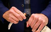 James Tidwell removes the cork from a wine bottle.(Vernon Bryant/Staff Photographer)