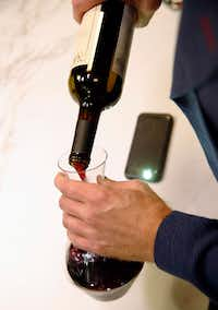 James Tidwell demonstrates how he uses the light on his smartphone while pouring wine into a decanter.(Vernon Bryant/Staff Photographer)