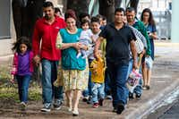 Volunteer Blanca Munoz carried 5-month-old Selene as she walked with the baby's father, Angel Bonilla (right) and other immigrants and their families from the McAllen Central Station to the Catholic Charities Humanitarian Respite Center.(Staff Photographer/Smiley N. Pool)