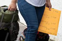 A woman carries an envelope marked with bus times as she heads from the bus station to the Catholic Charities Humanitarian Respite Center.(Staff Photographer/Smiley N. Pool)