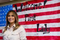 Melania Trump smiles after signing American flag artwork at the Upbring New Hope Children's Center in McAllen. Kids at the center also signed the flag.(Andrew Harnik/The Associated Press)