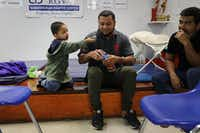 A Honduran father and son relaxed at the Catholic Charities Humanitarian Respite Center in McAllen on Thursday after recently crossing into the United States from Mexico.(Spencer Platt/Getty Images)