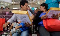 Guatemalans seeking asylum looked over travel packets as they waited at the bus station in McAllen on Thursday after they were processed and released by U.S. Customs and Border Protection.(Eric Gay/The Associated Press)