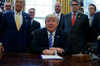 This March 24, 2017, file photo shows President Donald Trump, flanked by Commerce Secretary Wilbur Ross, left, and Energy Secretary Rick Perry. (Evan Vucci/The Associated Press)