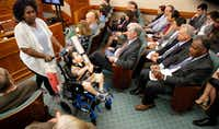 Mesquite mother Linda Badawo (left) pushed her medically fragile son, D'ashon Morris, past representatives of Superior HealthPlan (seated right) after testifying before the Texas House General Investigating and Ethics Committee in Austin on Wednesday.(Tom Fox/Staff Photographer)