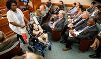 Mesquite mother Linda Badawo (left) pushed her medically fragile son, D'ashon Morris, past representatives of Superior HealthPlan (seated right) after testifying before the Texas House General Investigating and Ethics Committee in Austin on Wednesday. (Tom Fox/Staff Photographer)