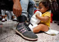 Damaris Gonzalez, 20, of Guatemala shows her ankle monitor that was attached by U.S. Border Patrol as they processed out of the McAllen, Texas facility. The monitor ensures that she will follow up to her court appointed hearing.  Damaris' father was killed and burned when she was younger. She and her 9 month-old son Yarlex (right) are waiting for their bus with other Central American immigrants at the Central Station bus terminal in downtown McAllen, Texas, Sunday, June 24, 2018. (Tom Fox/The Dallas Morning News)(Tom Fox/Staff Photographer)
