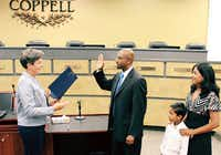 New Coppell City Council member Biju Mathew took the oath of office from Coppell Mayor Karen Hunt as his son, Noah, and wife, Shiji, close by. (Courtesy)