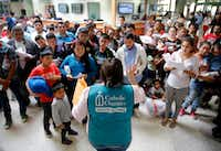 A staffer from Catholic Charities of the Rio Grande Valley gave instructions to Central Americans who were dropped off on government buses last month at the Central Station bus terminal in downtown McAllen.(Tom Fox/Staff Photographer)